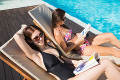 women-reading-books-sun-loungers-swimming-pool-side-view-two-young-43656341.jpg